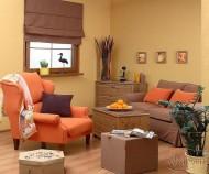 Kolory brązowy, beżowy i brzoskwiniowy tworzą we salonie niezwykle ciepły, a przy tym przytulny klimat. Klasyczna elegancja w tonacji brązu została ożywiona soczystym brzoskwiniowym kolorem, dając niezwykły efekt. Fot. dekoria.pl